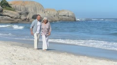 Elderly couple walking along the beach Stock Footage