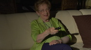 Elderly woman with TV remote changing channels Stock Footage