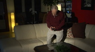 Elderly man sitting down on sofa and turns on TV Stock Footage