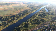 Pan from river on village above hot air balloon Stock Footage