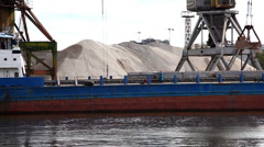 Crane unload gravel from barge on river Stock Footage