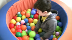 Little boy plays in ball pit Stock Footage