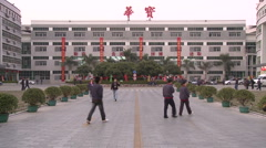 Chinese workers in China Donguan Shoe Factory - main building workers passing by - stock footage