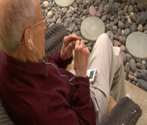 Elderly man with iPod put in earbuds Stock Footage