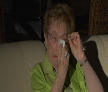Elderly woman watching TV cries and wipes tears from eyes Stock Footage