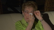 Stock Video Footage of Elderly woman watching TV cries and wipes tears from eyes