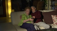 Elderly man helps wife use TV remote Stock Footage