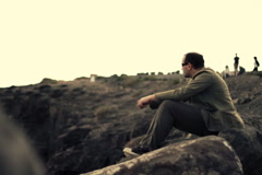 Pensive man sitting on stones and looking out to the sea  Stock Footage