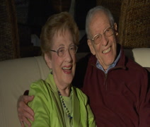 Affectionate elderly couple watching TV CU Stock Footage