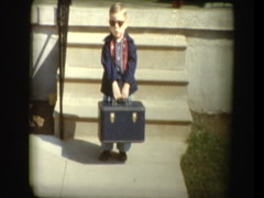 Adorable little boy in sunglasses with antique suitcase  - stock footage