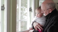 Stock Video Footage of Grandfather holding his granddaughter near window