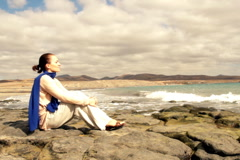 Young woman sitting on stones and thoughtfully looking out to sea  Stock Footage