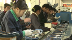 Chinese workers in China Donguan Shoe Factory - workers finishing shoes - stock footage