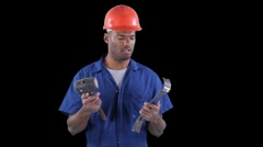Worker tries to figure out how to use crowbar and hammer together - stock footage