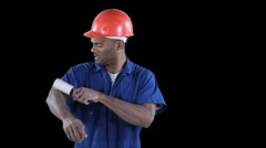 Blue collar worker start cleaning his jump suit with roller - frustrated Stock Footage