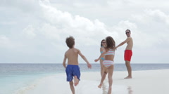 Young family of four walking on the beach Stock Footage