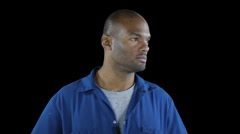 Black man in workers jumpsuit - looks to left seriously and turns back to camera - stock footage