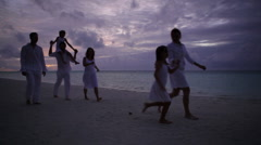People walking on beach after sunset Stock Footage