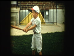 Cute little boy in baseball uniform swings bat Stock Footage