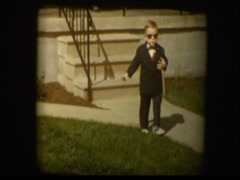 Cute little boy dressed up in suit and sunglasses poses for camera Stock Footage
