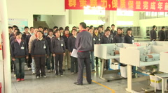 Chinese workers in China Donguan Shoe Factory - workers singing factory song Stock Footage