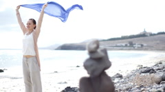 Attractive Woman with waving blue sarong at the beach, shot at 60fps, pan shot Stock Footage