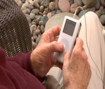 Arthritic Elderly mans hands with iPod CU Stock Footage
