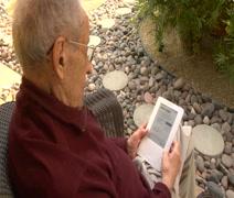 Elderly man reading kindle OTS Stock Footage