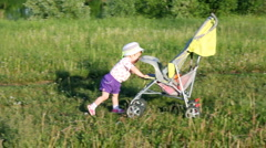 child pushes stroller on summer lawn - stock footage