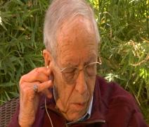Elderly man puts in earbuds CU Stock Footage