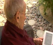 Elderly man reading on Kindle Stock Footage
