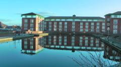Zoom in - large urban office block reflection in canal basin Mallard bathing. Stock Footage