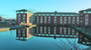 Stock Video Footage of Zoom in - large urban office block reflection in canal basin Mallard bathing.