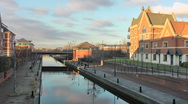 Stock Video Footage of Modern apartments beside urban canal, low warm sunlight.