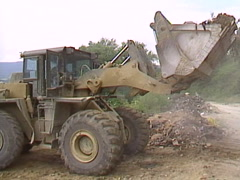 Military, army front end loader and truck clearing war debris  Stock Footage