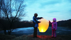 Boy and girl holding, gently touch chinese lantern in winter woods Stock Footage