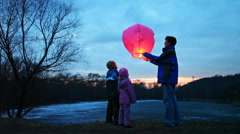 Man starts chinese lantern of  forest, its son and daughter look at it, part4 Stock Footage