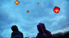 boy and girl look from below upwards on flying glowing chinese lanternes - stock footage