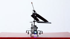 toy helicopter is on table, its blades start to rotate, then it flies up upwards - stock footage