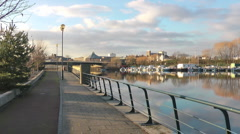 Urban River footpath with boat yard and bridge. Stock Footage
