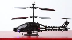 Toy helicopter is on table, its blades rotate, then flies up upwards, downwards Stock Footage