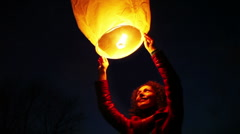 Woman holds above head glowing chinese lantern Stock Footage