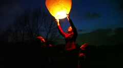 Woman holds glowing chinese lantern, son and daughter look Stock Footage