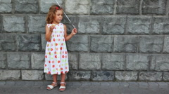 Little girl stands, eats ice cream Stock Footage
