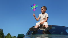 boy sitting on roof of car, holding in hand toy from seven decks - stock footage