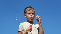 Boy inflates large bubbles Stock Footage