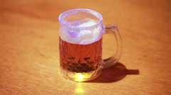 Transparent cup of beer standing on wooden table Stock Footage
