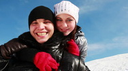 Stock Video Footage of boy and girl standing outdoors in winter, she hugs it from behind neck