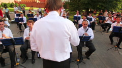 Conductor controls brass band in Alexander's Garden Stock Footage