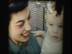 Proud 50's mom holds new born infant Stock Footage